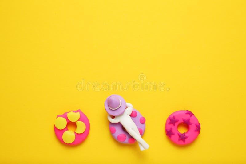 Gente de la plastilina que se relaja en lilo inflable del buñuelo en piscina Relajación y días de fiesta del verano de la histori imagenes de archivo