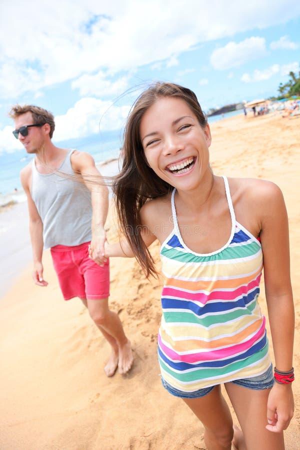 Gente de la playa - pares jovenes que celebran caminar de las manos imágenes de archivo libres de regalías