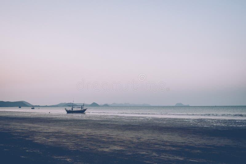 Gente de la silueta que camina en la playa en la opinión de la puesta del sol Playa y montañas que pasan por alto el océano Barco foto de archivo