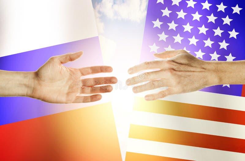 Gente de las manos contra las banderas Rusia y los E.E.U.U. del contexto fotos de archivo