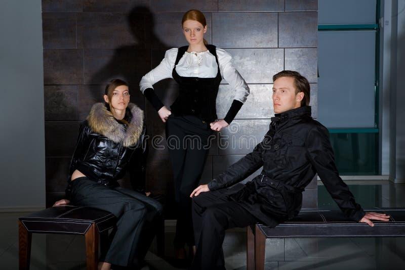 Gente de moda en sitio con colores oscuros foto de archivo