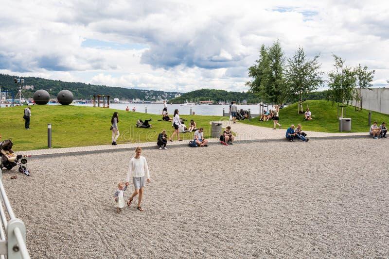 Gente de Oslo en la playa Aker Brygge del puerto imagen de archivo libre de regalías