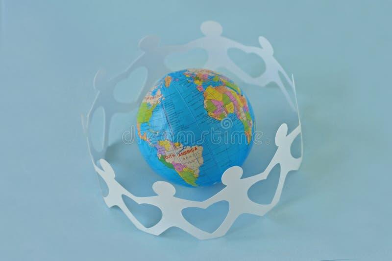 Gente de papel en un círculo alrededor del globo de la tierra en fondo azul - imagen de archivo