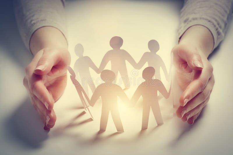 Gente de papel rodeada por las manos en el gesto de la protección Concepto de seguro fotografía de archivo libre de regalías