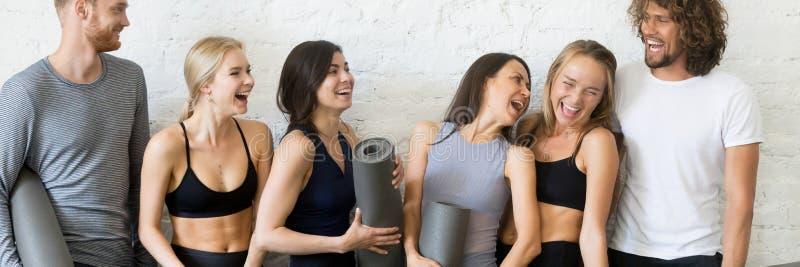 Gente de risa que descansa después de la situación del entrenamiento en fila cerca de la pared fotos de archivo