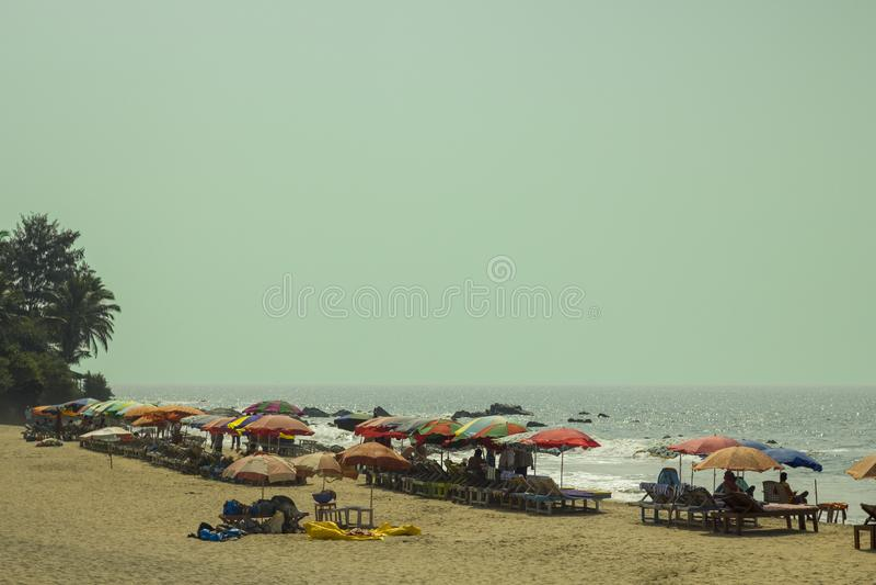 Gente debajo de los parasoles de playa multicolores en la arena amarilla en ociosos del sol en el fondo del océano debajo de un a fotografía de archivo libre de regalías