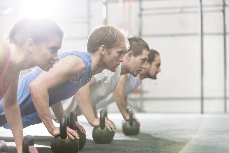 Gente dedicada que hace flexiones de brazos con los kettlebells en el gimnasio del crossfit imágenes de archivo libres de regalías