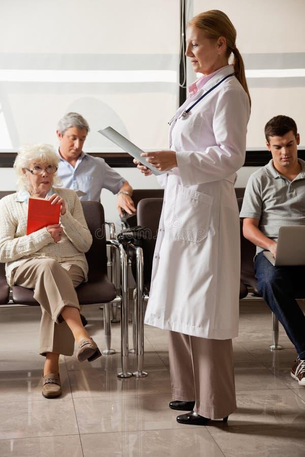 Gente del doctor Reading File With en pasillo foto de archivo