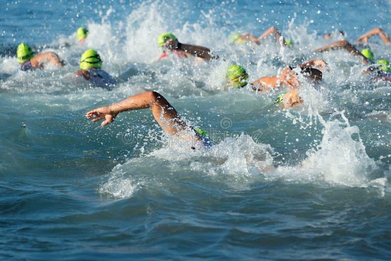 Gente del grupo en la natación del wetsuit en el triathlon imagen de archivo libre de regalías