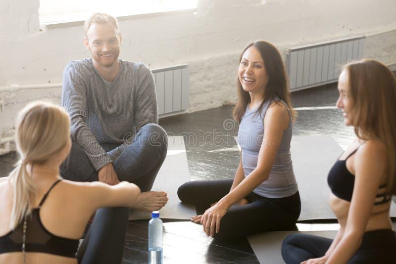 Gente deportiva de risa que tiene lección de la yoga de la charla del equipo fotos de archivo libres de regalías