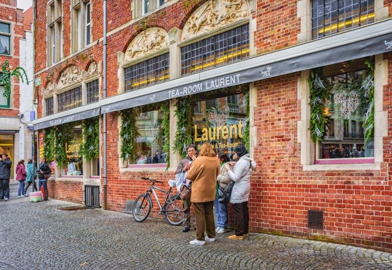 Gente desconocida que come una comida ligera cerca del sitio Laurent del té en Sint-Salvatorskerkhof Brujas, Bélgica imágenes de archivo libres de regalías