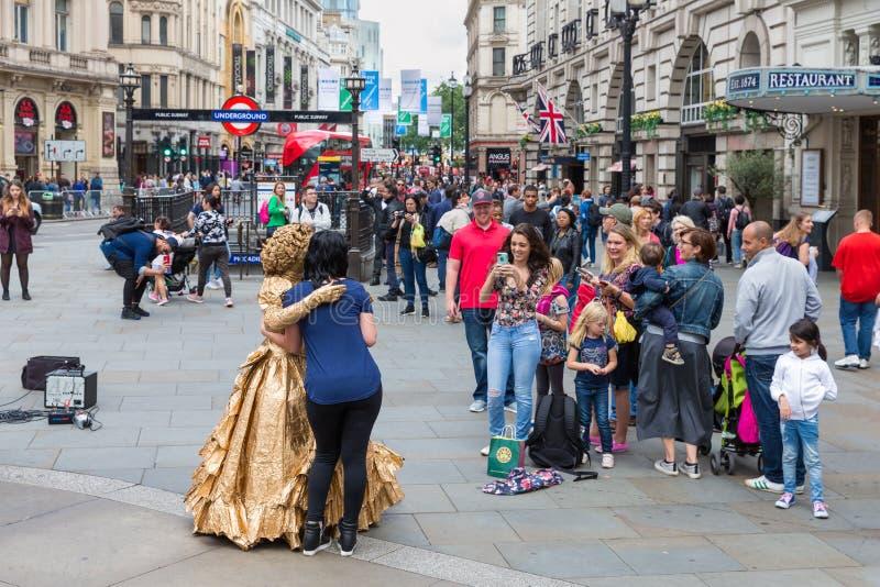 Gente desconocida que hace imágenes de la estatua viva en Piccadilly Circ imagen de archivo libre de regalías
