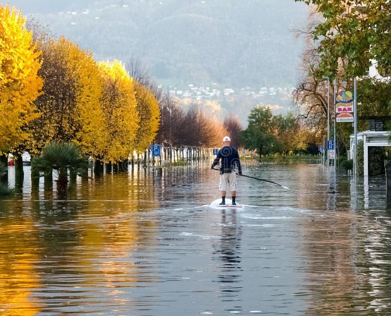 Gente desconocida que practica surf en el camino inundado imagen de archivo libre de regalías