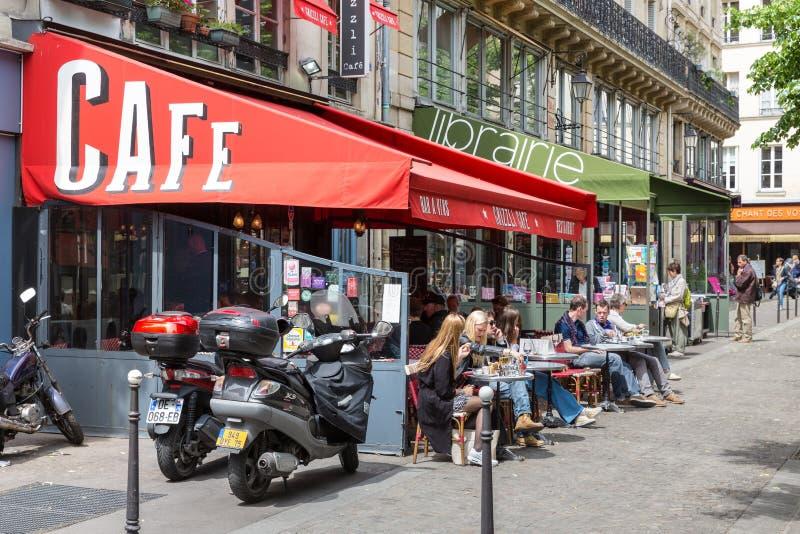 Gente desconocida que se sienta en una terraza en el centro de la ciudad en París, Francia imagenes de archivo