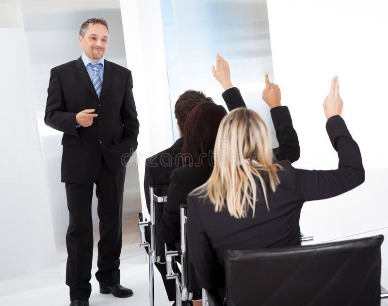 Gente di affari alla conferenza che fa le domande fotografie stock