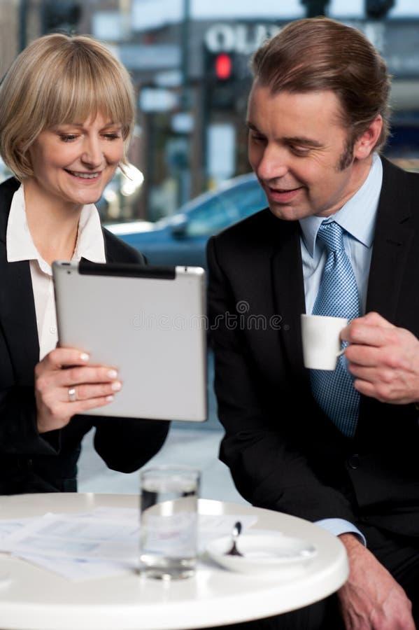 Gente di affari allegra che per mezzo della compressa digitale immagini stock libere da diritti