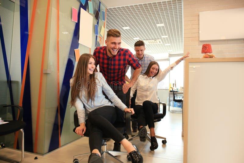 Gente di affari allegra nell'abbigliamento casual astuto divertendosi mentre correndo sulle sedie e sul sorridere dell'ufficio fotografia stock