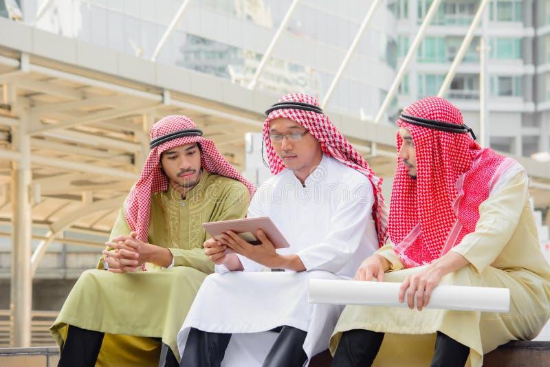 Gente di affari araba che si siede e che ha consultazione usando compressa fotografie stock libere da diritti