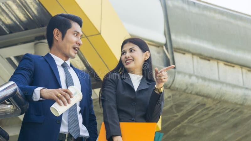 Gente di affari asiatica astuta conversazione e gioia della lavoratrice e dell'uomo a fotografia stock libera da diritti