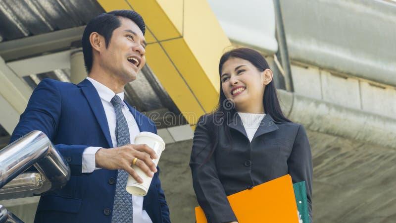 Gente di affari asiatica astuta conversazione e gioia della lavoratrice e dell'uomo a fotografie stock libere da diritti