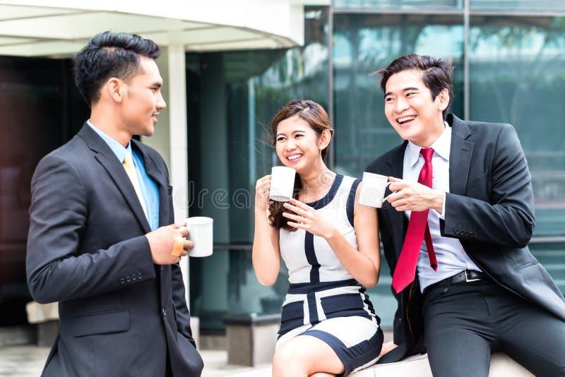 Gente di affari asiatica che beve caffè fuori immagini stock