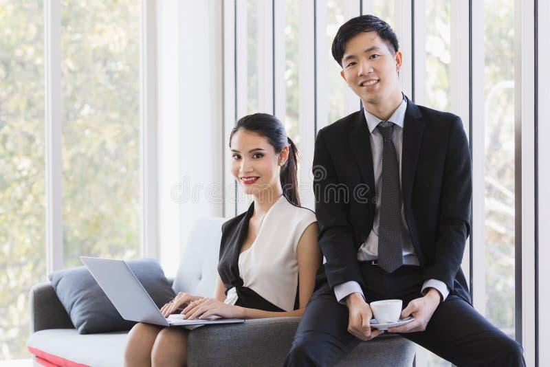 Gente di affari asiatica che posa nell'ufficio immagine stock libera da diritti