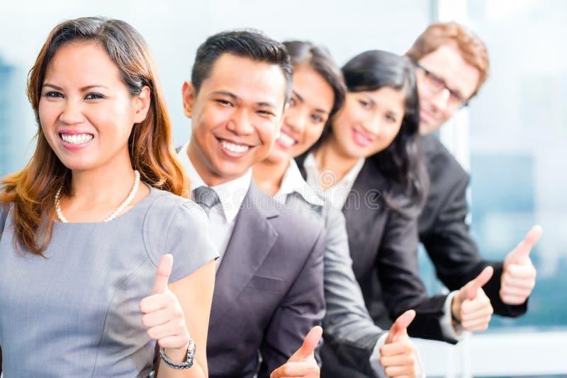 Gente di affari asiatica che sta nella fila in ufficio immagini stock