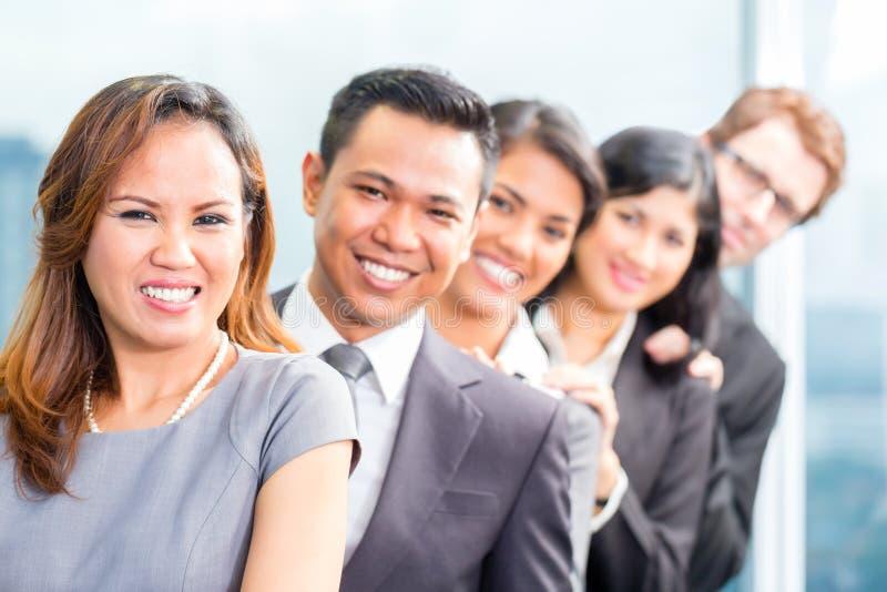 Gente di affari asiatica che sta nella fila in ufficio immagine stock libera da diritti