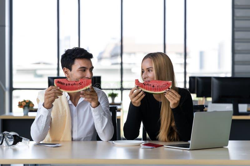 Gente di affari caucasica attraente che mangia anguria in ufficio Concetto di vacanze estive fotografia stock libera da diritti