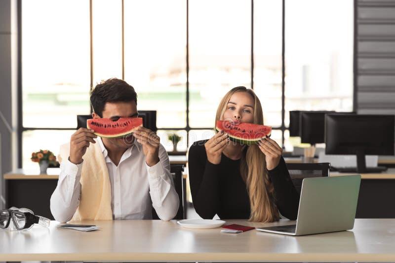 Gente di affari caucasica attraente che mangia anguria in ufficio Concetto di vacanze estive fotografie stock libere da diritti