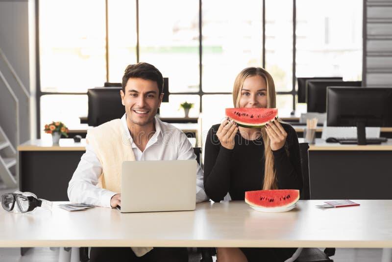 Gente di affari caucasica attraente che mangia anguria in ufficio Concetto di vacanze estive immagine stock libera da diritti
