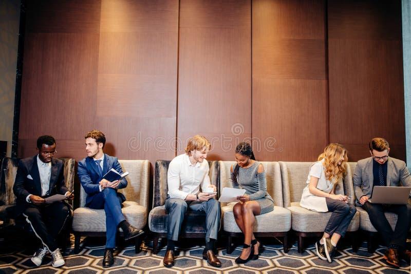 Gente di affari che aspetta intervista di lavoro, parlante fotografia stock