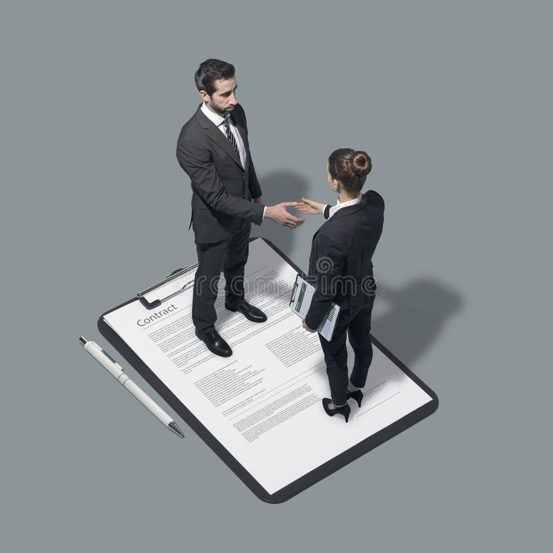 Gente di affari che firma un contratto e che stringe le mani fotografia stock