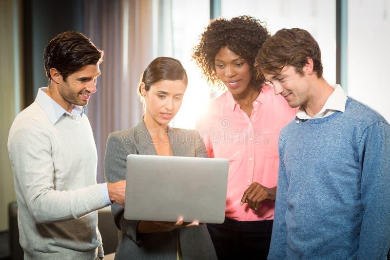 gente di affari che ha discussione sopra il computer portatile fotografia stock libera da diritti