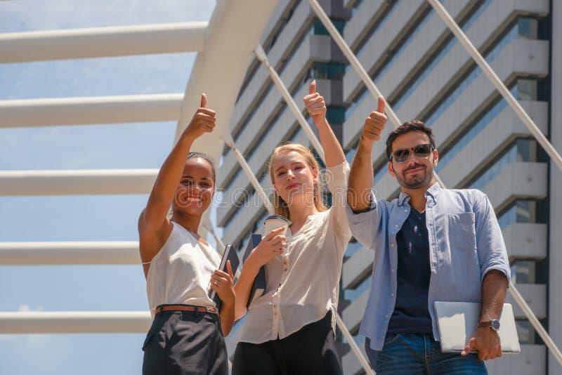 Gente di affari che ha pollice sullo spirito di gruppo di manifestazione di tp di successo insieme all'aperto fotografia stock