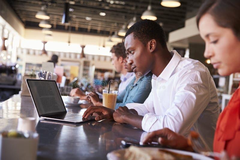 Gente di affari che lavora al contatore in caffetteria fotografia stock