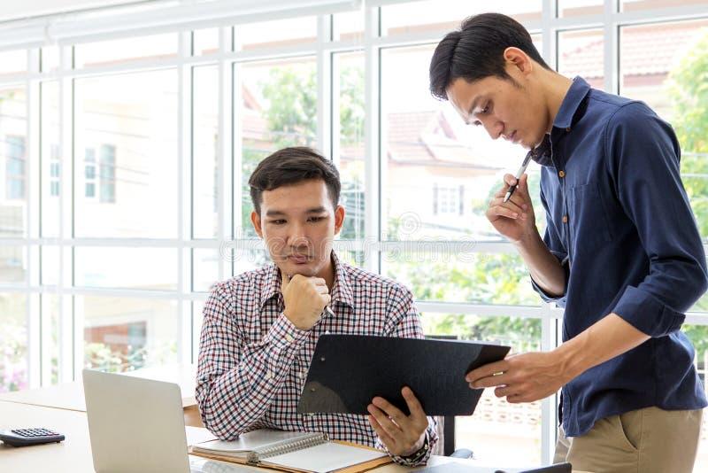 Gente di affari che lavora e che discute nell'ufficio Due maschio U immagini stock