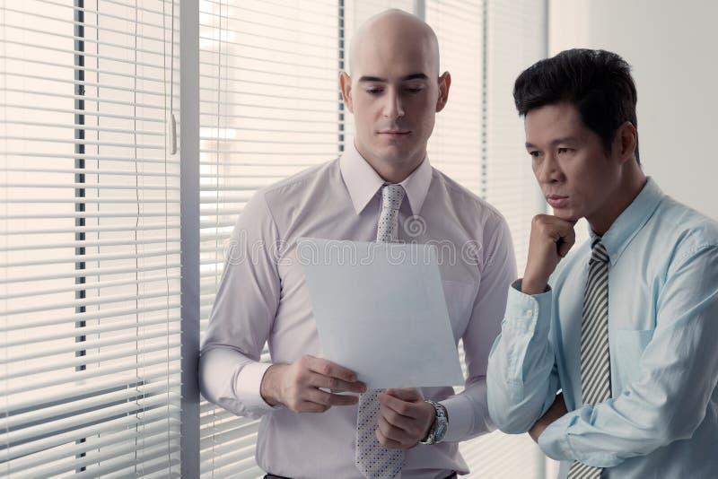 Gente di affari che legge documento fotografia stock libera da diritti