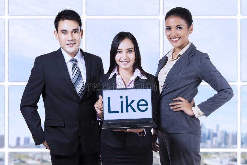 Gente di affari che mostra come sul computer portatile fotografia stock