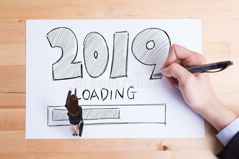 Gente di affari che scrive il testo 2019 di caricamento sulla carta e la donna che lo indicano immagini stock