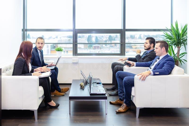 Gente di affari che si siede alla riunione di lavoro in ufficio corporativo moderno fotografia stock libera da diritti