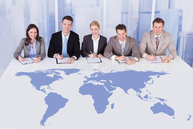 Gente di affari che si siede alla tavola di conferenza con la mappa di mondo fotografie stock