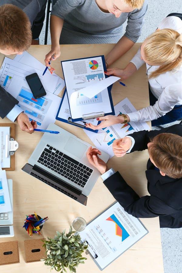 Gente di affari che si siede e che discute alla riunione d'affari, nell'ufficio fotografia stock libera da diritti