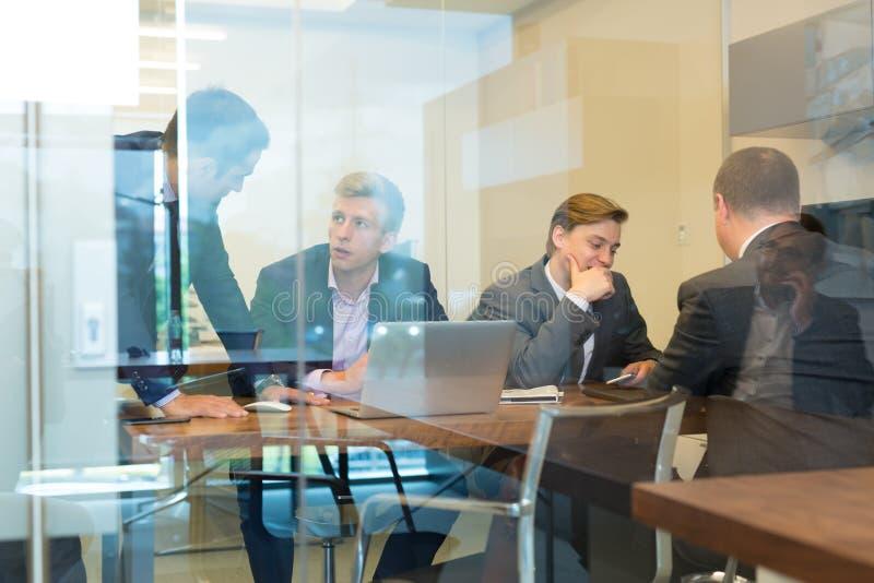 Gente di affari che si siede e che confronta le idee alla riunione corporativa fotografia stock libera da diritti