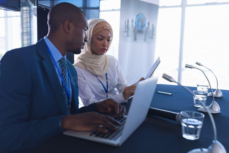 Gente di affari che si siede insieme alla tavola nella riunione di conferenza fotografie stock libere da diritti