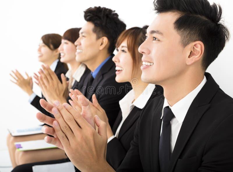Gente di affari che si siede in una fila e che applaude fotografia stock libera da diritti