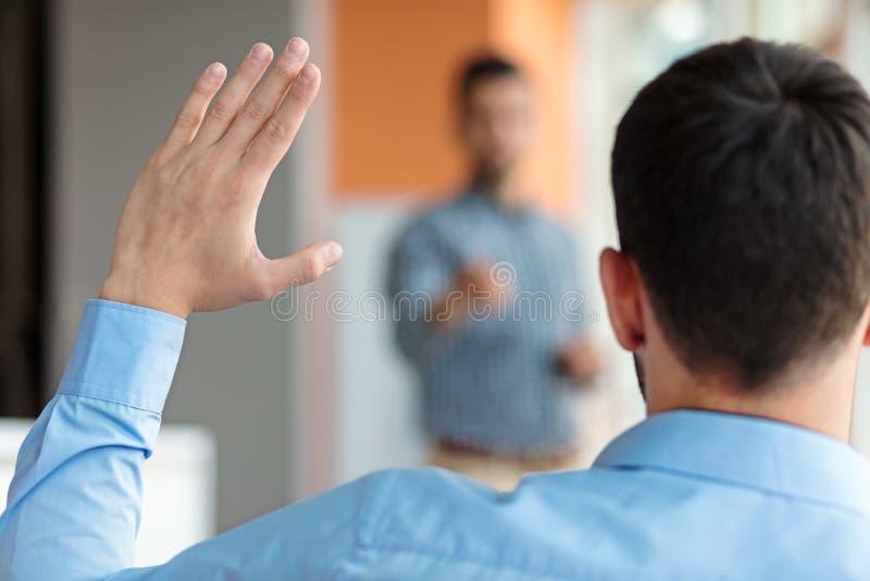 Gente di affari che solleva là mano su ad una conferenza per rispondere ad una domanda fotografie stock