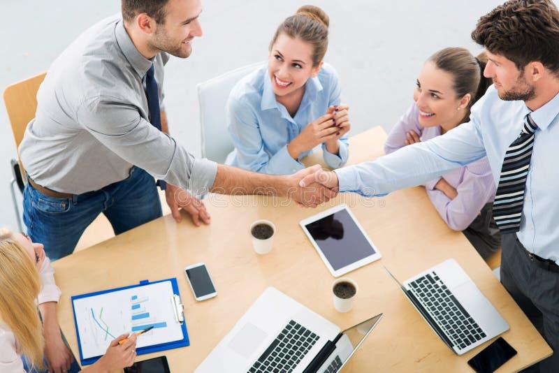 Gente di affari che stringe le mani attraverso la tavola immagine stock