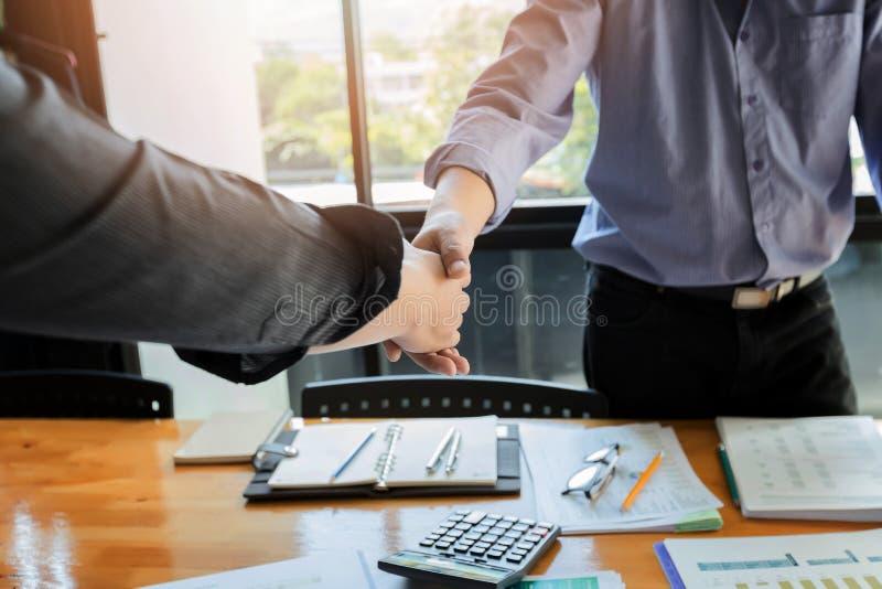 Gente di affari che stringe le mani che finiscono su una riunione immagini stock