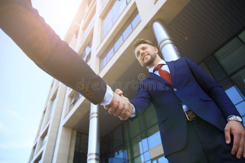 Gente di affari che stringe le mani fuori dell'edificio per uffici moderno fotografie stock libere da diritti